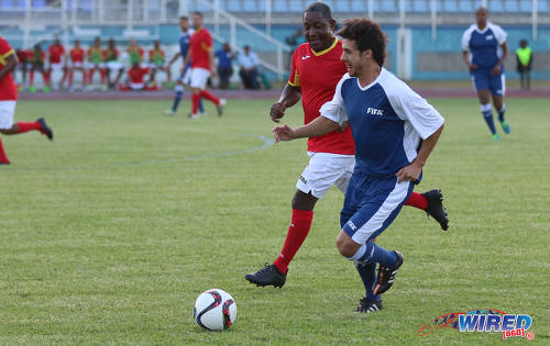 Photo: Former Argentina World Cup star Pablo Aimar (right) runs at Trinidad and Tobago 2006 World Cup midfielder Russell Latapy during an exhibition match at the Ato Boldon Stadium in Couva on 10 April 2017. (Courtesy Sean Morrison/Wired868)