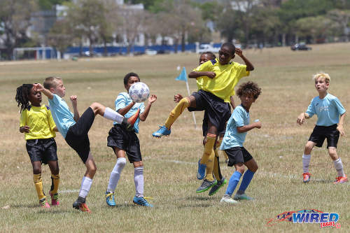Photo: QPCC '1' midfielder Logan Maingot (second from left) challenges a Trendsetter Hawks '2' for the ball while his teammates Cayden Trestrail (far right) and Luke Correia (second from right) look on at the Queen's Park Savannah on 22 April 2017. QPCC won 5-1. (Courtesy Sean Morrison/Wired868)