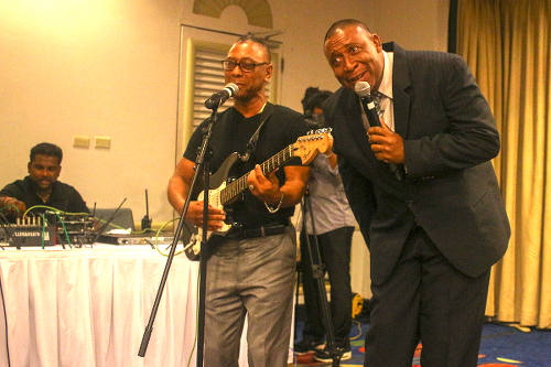 Photo: Trinidad and Tobago Football Association (TTFA) president David John-Williams (right) performs a duet with former Calypso Monarch, Cro Cro, at the launch of the National Elite Youth Development Program at the Trinidad Hilton on 14 October 2016.