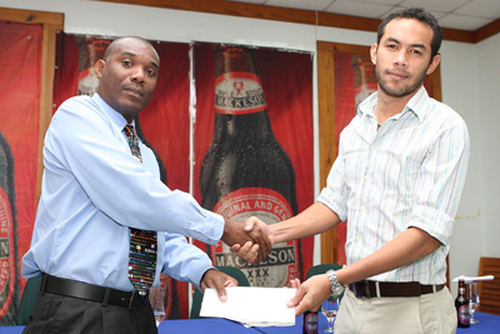 Photo: Ex-Super 10 Basketball League (SBL) managing director and commissioner Keith Clement (left) receives a cheque from Mackeson brand manager Dominic Lau. Clement is also sport editor at the Trinidad Guardian. (Copyright Trinidad Guardian)