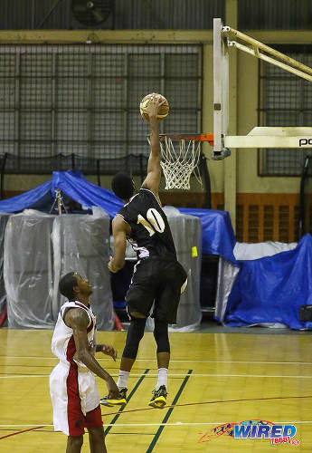 Photo: A Petro Jazz player dunks the ball during basketball action against UTT. (Courtesy Sean Morrison/Wired868)