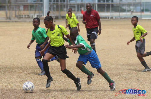 Photo: Adrenaline FA attacker Lu Ann Craig (left) takes on the Febeau Government Primary defence during RBNYL Under-11 action at Constantine Park in Macoya on 6 May 2017. (Courtesy Sean Morrison/Wired868)
