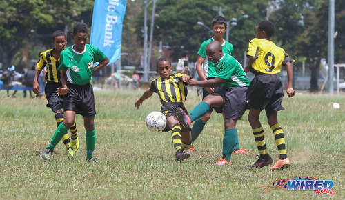 Photo: Harvard SC midfielder Ethan Paponette (left) looks on his teammate tries to force the ball past two RSSR players during RBNYL North Zone U-13 action at the Queen's Park Savannah in Port of Spain on 27 May 2017. (Courtesy Sean Morrison/Wired868)