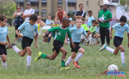 Photo: Harvard SC attacker Josh Miguel (centre) takes on four QPCC '2' players singlehandedly during RBNYL North Zone U-11 action at the Queen's Park Savannah in Port of Spain on 27 May 2017. (Courtesy Sean Morrison/Wired868)