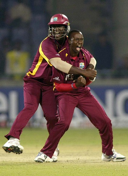 Photo: West Indies pacer Kemar Roach (right) celebrates with captain Darren Sammy.