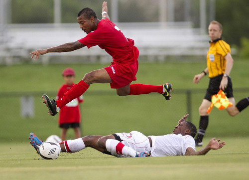 Photo: Trinidad and Tobago winger Lester Peltier hurdles a Canadian opponent during a friendly international this year.  (Courtesy AP)