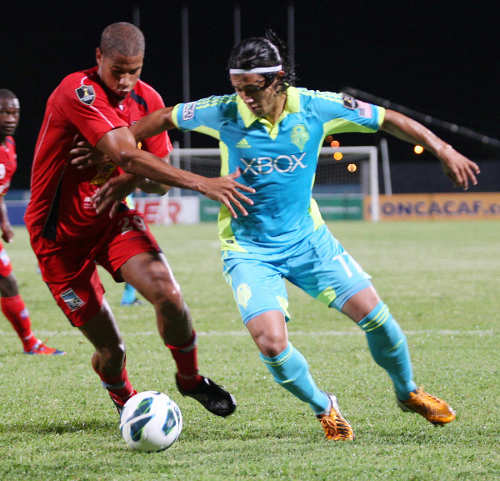 Photo: Former Caledonia AIA defender Radanfah Abu Bakr (left) battles Seattle Sounders striker Fredy Montero during 2012 CONCACAF Champions League action. Abu Bakr, who now plays in Kazakhastan, is expected to start tomorrow. (Courtesy Wired868)