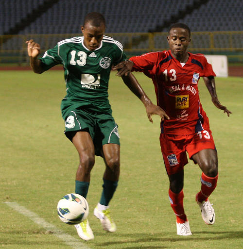 Photo: DirecTV W Connection defender Kern Cupid (left) screens the ball away from Neal & Massy Caledonia AIA winger Trayon Bobb. Bobb, a Guyana international, is set to move to the Finland Third Division. (Courtesy Photos868)