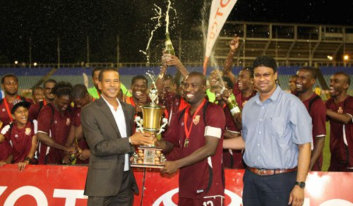 Photo: North East Stars acting captain Cornell Glen (centre) takes the Toyota Classic trophy from Pro League CEO Dexter Skeene. But is it enough to justify the outlay of club owner Darryl Mahabir? (Courtesy Wired868)