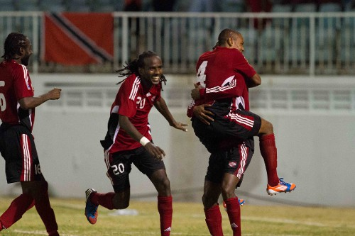 "Photo: Trinidad and Tobago defender Seon Power (left) rushes in to share the love as the ""Soca Warriors"" celebrate their Caribbean Cup semifinal triumph over Martinique. (Courtesy Allan V. Crane/ Wired868)"