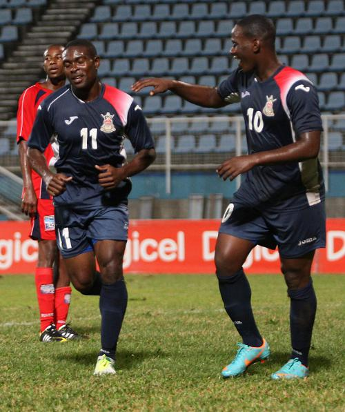 Photo: Defence Force winger Kevon Carter (left) is congratulated by teammate Devorn Jorsling during a previous fixture. (Courtesy Wired868.com)