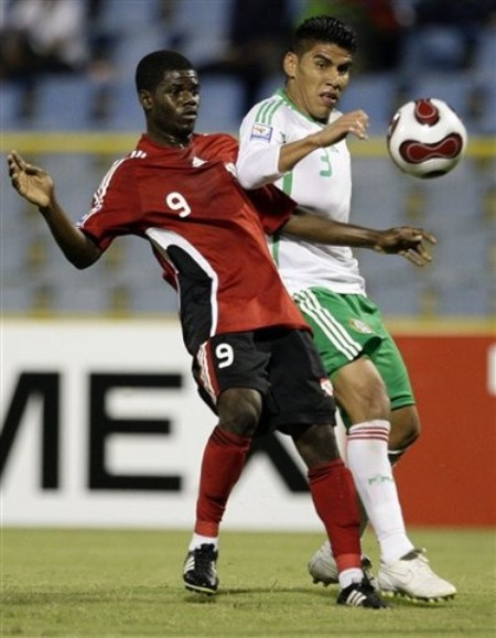 Photo: Trinidad and Tobago midfielder Hughtun Hector (left) challenges Mexico defender Carlos Salcido during the 2010 World Cup qualifying campaign. (Courtesy AP)