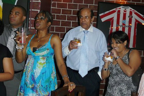 Photo: Reshmi Ramnarine (far right) shares a drink with former Education Minister Dr Tim Gopeesingh.