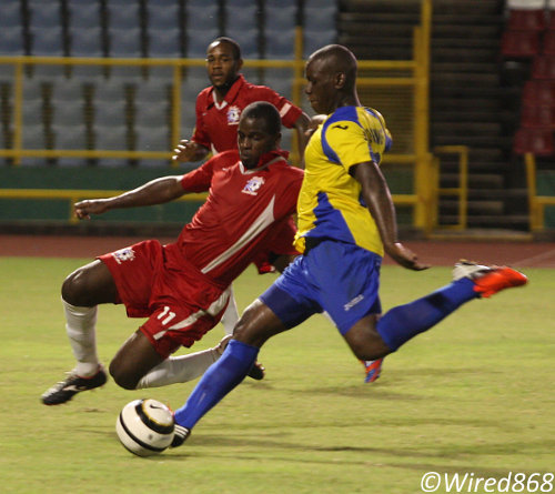 Photo: Defence Force striker Devorn Jorsling (right) goes for goal during a previous fixture against St Ann's Rangers. (Courtesy Wired868)