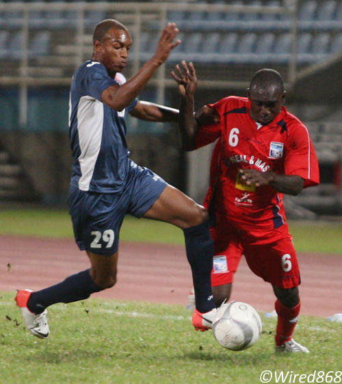 Photo: Caledonia AIA striker Trevin Caesar (right) holds off Defence Force winger Jemel Sebro during a previous Pro League fixture. (Courtesy Wired868)