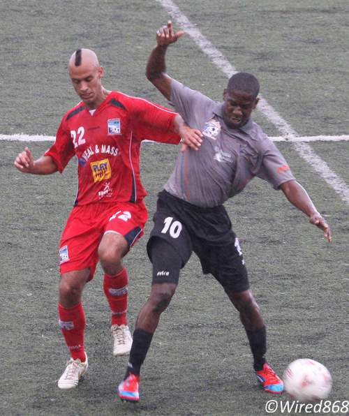 Photo: Caledonia AIA midfielder Miguel Romeo (left) tries to outmuscle St Ann's Rangers attacker Devon Modeste. (Courtesy Wired868)
