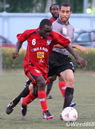 Photo: Caledonia AIA striker Trevin Caesar (left) runs at goal while St Ann's Rangers defender Musa Nakhid tries to keep up. (Courtesy Wired868)