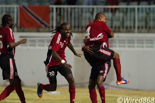 Photo: Trinidad and Tobago defender Seon Power (second from left) sprints in to join the celebration during the 2012 Caribbean Cup finals in Antigua. (Courtesy Allan V. Crane/ Wired868)