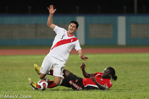 Photo: Trinidad and Tobago forward Kenwyne Jones (right) chops down Peru defender Carlos Zambrano. (Courtesy Allan V. Crane/ Wired868)