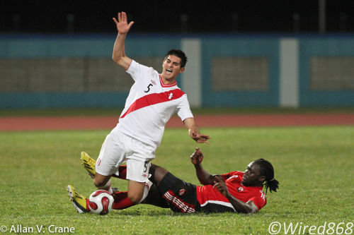 Photo: Trinidad and Tobago forward Kenwyne Jones (right) catches Peru defender Carlos Zambrano with a late tackle. (Courtesy Allan V. Crane/ Wired868)