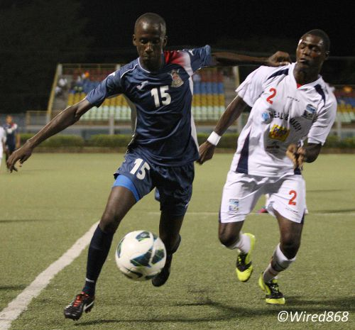 Photo: Defence Force midfielder Jerwyn Balthazar (left) takes on Caledonia AIA defender Aubrey David. (Courtesy Wired868)