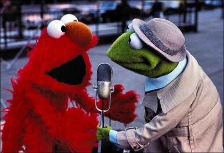 "Photo: Not everyone can pull off a ""doorstep."" Notice Kermit (right) has Elmo out in the open and away from any doors while he gets the microphone nice and close for any possible insults."