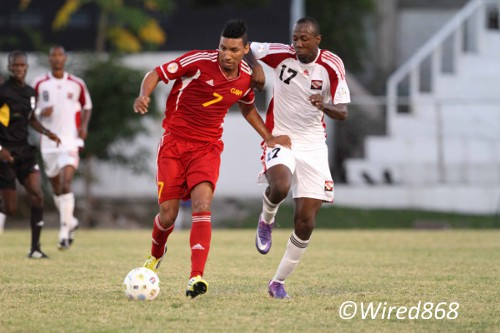 Photo: Trinidad and Tobago defender Daneil Cyrus (right) gets a grip on Cuban attacker Marcel Hernandez during the 2012 Caribbean Cup final. (Courtesy Allan V. Crane/Wired868)