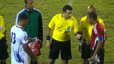 Photo: Belizean referee Irfan Basdemir (centre) gives it a toss while Trinidad and Tobago captain Densill Theobald (far right) and Belize captain Dalton Eiley (far left) look on. (Courtesy TTFF Media)