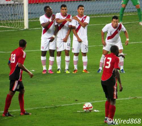 Photo: Trinidad and Tobago attacker Cornell Glen (right) and Densill Theobald line up a free kick against Peru. (Courtesy Juliet Solomon/Wired868)