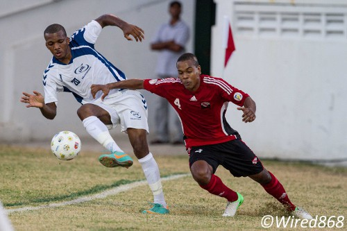 Photo: Trinidad and Tobago defender Curtis Gonzales (right) leans on a Martinique attacker during the 2012 Caribbean Cup finals. (Courtesy Allan V. Crane/Wired868)
