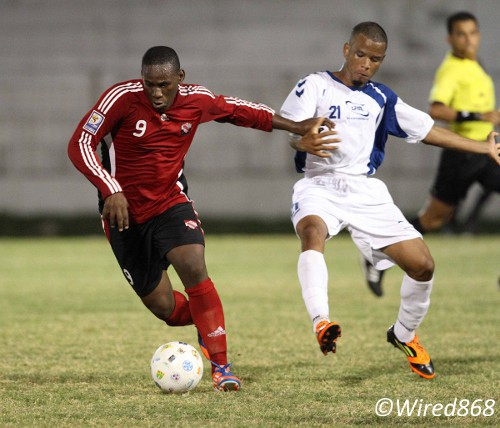 Photo: Trinidad and Tobago striker Devorn Jorsling (left) holds off a Martiniquan defender during the 2012 Caribbean Cup (Courtesy Allan V. Crane/Wired868)