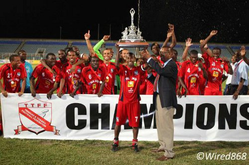 Photo: Caledonia AIA captain Stephan David (centre) takes the 2012/2013 FA Trophy from TTFF president Raymond Tim Kee. But the massive trophy did not come with a cash prize. (Courtesy Wired868)