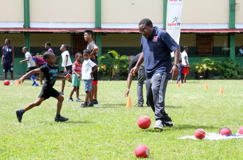 Photo: Former Trinidad and Tobago co-head coach and Caledonia AIA co-founder Jamaal Shabazz (right) helps out at a SPORTT Company Easter Camp. (Courtesy SPORTT Company)