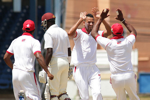 Photo: Trinidad and Tobago's Rayad Emrit (second from right) celebrates a wicket during a first-class contest. (Courtesy WICB Media)