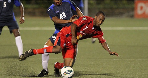 Photo: Caledonia AIA captain Stephan David is knocked over by Police midfielder Kenaz Williams. (Courtesy TT Pro League)