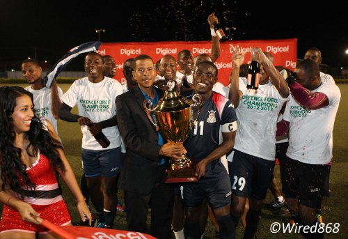 Photo: Pro League CEO Dexter Skeene (centre) hands the 2012/13 Pro League trophy over to stand-in Defence Force captain Kevon Carter. Rawle Fletcher was a regular first team member of the Defence Force football team over the last four seasons. (Courtesy Wired868)