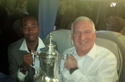 Photo: Former Trinidad and Tobago international defender Dennis Lawrence (left) poses with England's FA trophy.