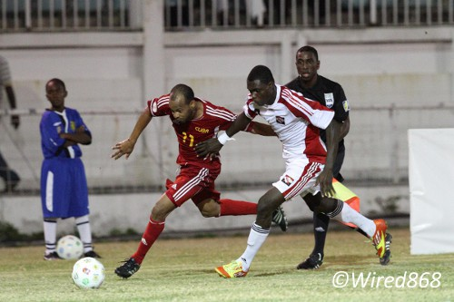 Photo: Trinidad and Tobago defender Aubrey David (right) tries to keep up with Cuban winger Ariel Martinez during the 2012 Caribbean Cup final. (Courtesy Allan V. Crane/ Photos868)