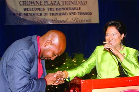 Photo: Ex-Sport Minister Anil Roberts (left) pays his respects to then Prime Minister Kamla Persad-Bissessar.