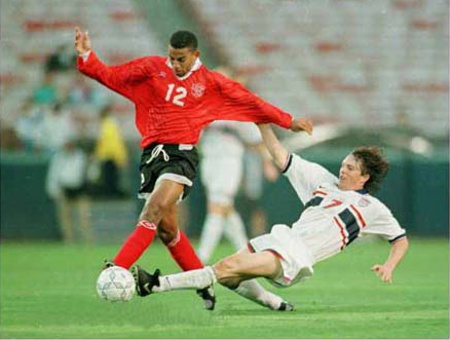 Photo: Ex-T&T midfielder David Nakhid (left) in action against the United States. Nakhid was the first Trinidad and Tobago player to participate in UEFA club competition. But he was denied the chance to represent his country until in his 30's.