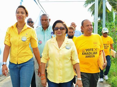 Photo: Then Prime Minister Kamla Persad-Bissessar (centre) and candidate Khadijah Ameen (left) walk-about during the UNC's unsuccessful by-election campaign in Chaguanas West. (Courtesy Jyoti Communications)