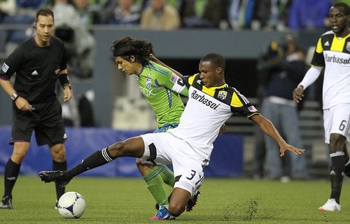 Photo: Columbus Crew midfielder Kevan George (right) tackles Seattle Sounders attacker Fredy Montero.