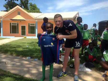 Photo: Walsall midfielder Sam Mantom (right) gives a Tobago boy the gift of a replica jersey. (Courtesy Walsall Facebook page)