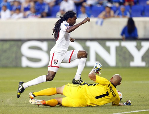 Photo: Trinidad and Tobago midfielder Keon Daniel goes around El Salvador goalkeeper Dagoberto Portillo during the 2013 CONCACAF Gold Cup (Courtesy YahooSports)