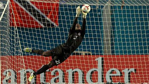 Photo: Trinidad and Tobago goalkeeper Jan-Michael Williams fends away a long range missile against Haiti. (Courtesy ESPN)