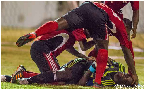 Photo: Trinidad and Tobago goalkeeper Jan-Michael Williams (bottom) is congratulated for his heroics during the 2012 Caribbean Cup. (Courtesy Allan V. Crane/ Wired868)