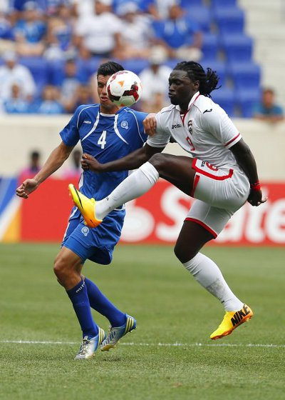Photo: Trinidad and Tobago forward Kenwyne Jones (right) tries to control the ball under pressure from El Salvador defender Steven Purdy. (Courtesy CONCACAF)