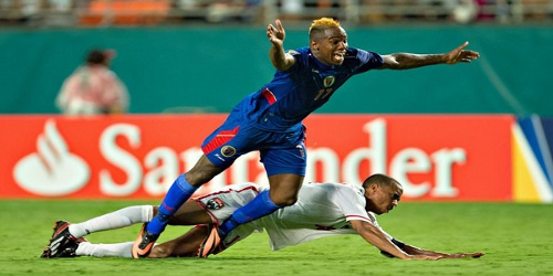 Photo: Trinidad and Tobago captain Densill Theobald (bottom) manages to check Haiti striker Jean Maurice's progress during the 2013 Gold Cup. (Courtesy CONCACAF)