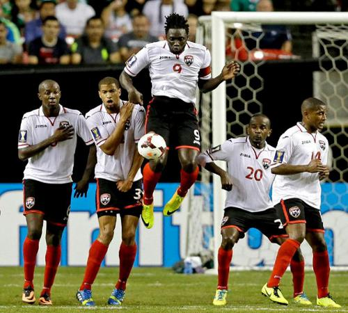 Photo: Trinidad and Tobago players (from left) Daneil Cyrus, Radanfah Abu Bakr, Kenwyne Jones, Seon Power and Andre Boucaud try to keep out a Mexico free kick during the 2013 CONCACAF Gold Cup. (Courtesy YahooSports)