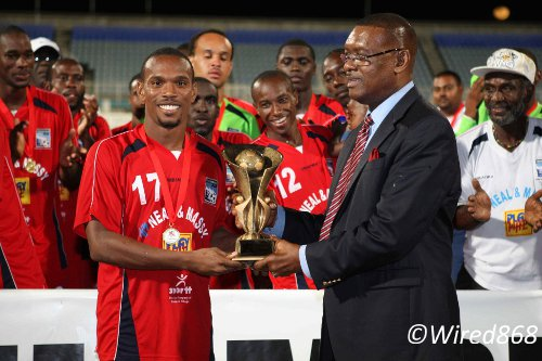 Photo: Caledonia AIA midfielder Akim Armstrong (left) receives his 2013 TTFF FA Trophy MVP award from TTFF president Raymond Tim Kee. (Courtesy Wired868)